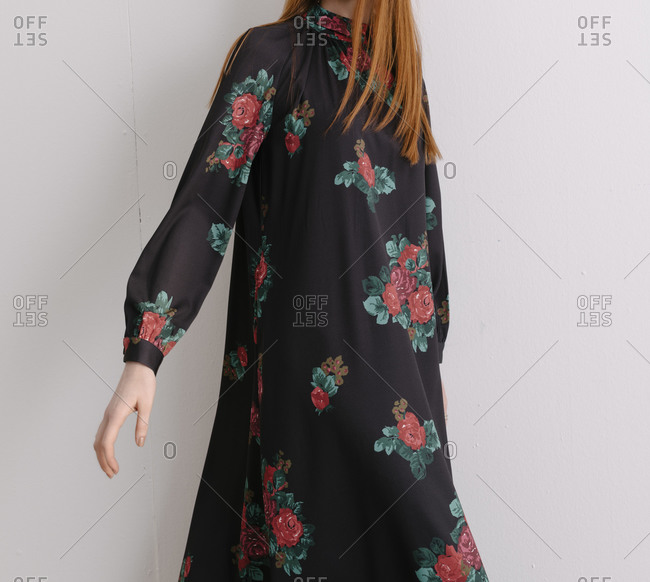 Young model wearing a black dress with red floral pattern extending her hand out