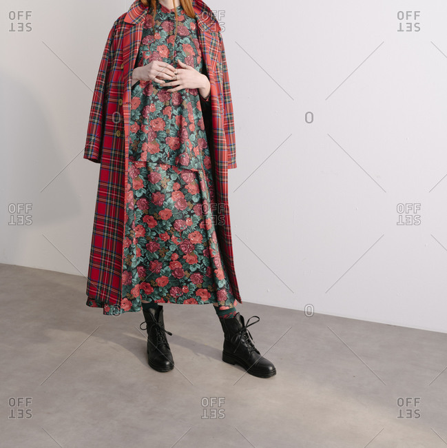A young model wearing a red plaid designer jacket over floral dress