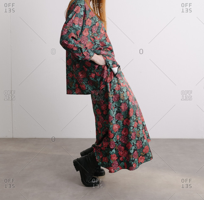 Studio shot of a young model wearing a red plaid floral designer dress and leaning forward