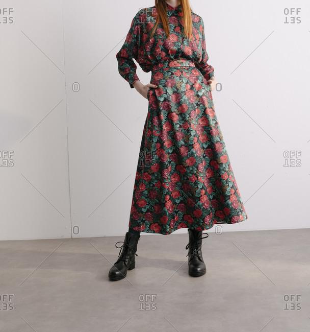 Young model wearing a red plaid floral designer dress with her hands in her pockets