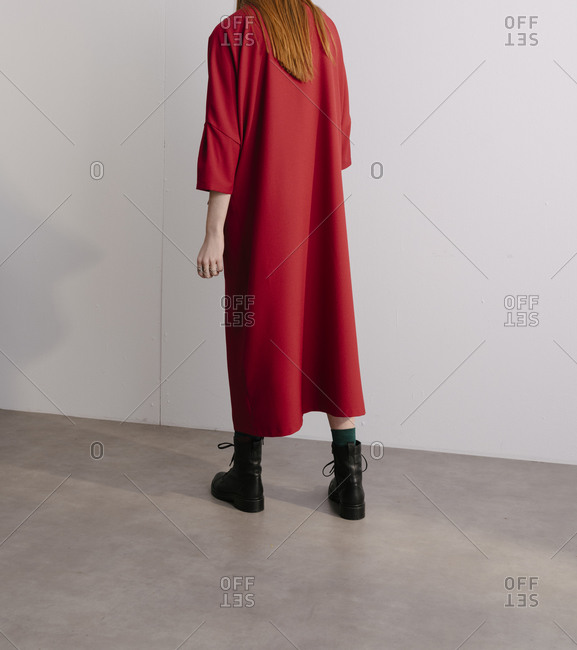 Rear view of model wearing designer red coat and combat boots