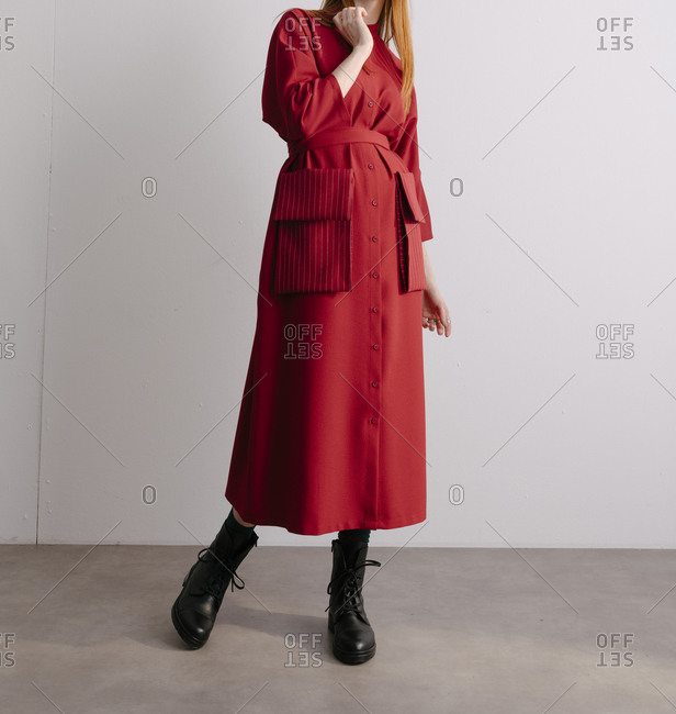 Young model wearing red designer trench coat and combat boots