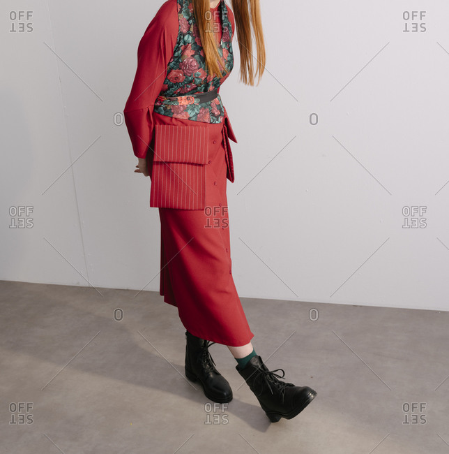 Stylish young model wearing red designer outfit with floral vest