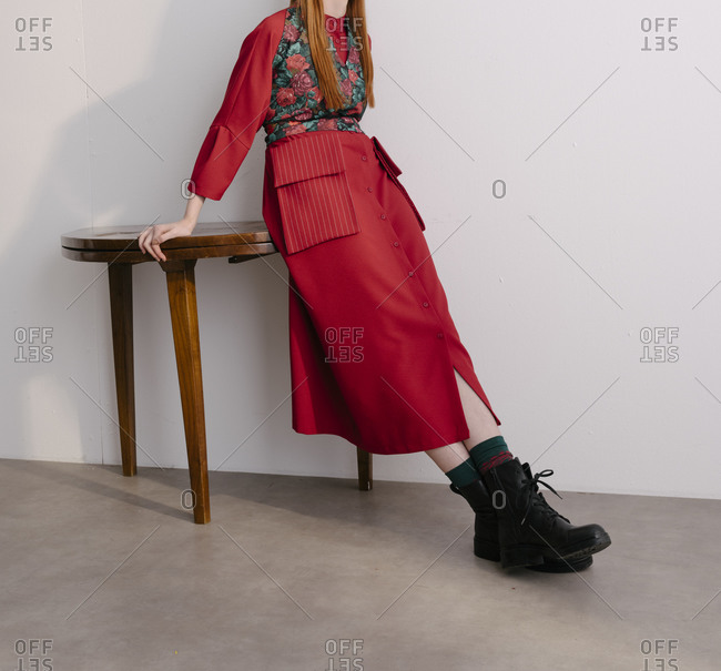Model wearing red designer outfit with floral vest sitting on edge of wooden table