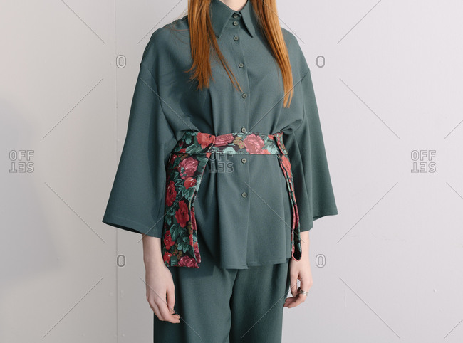 Female model wearing a green designer outfit with floral belt