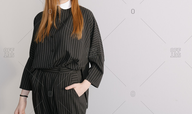 Model wearing designer black striped suit with hand in her pocket