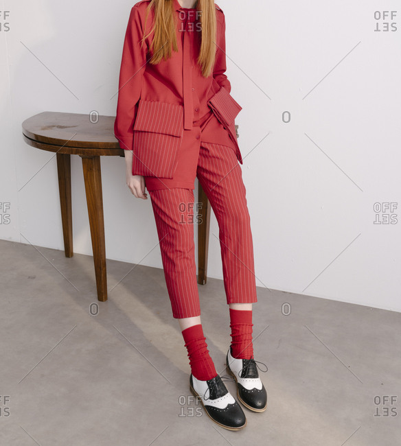 Fashionable woman dressed in a red designer suit sitting on wooden table