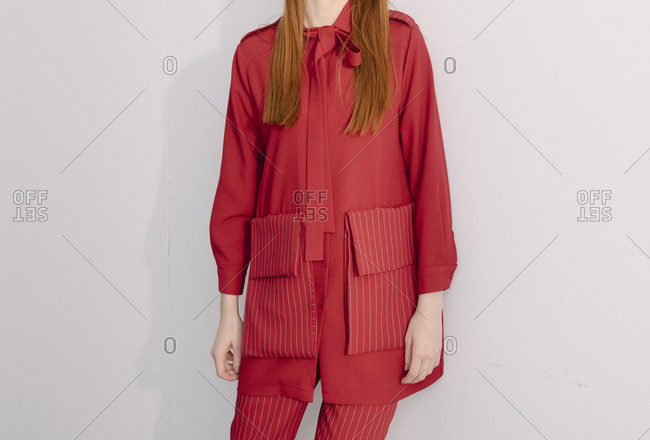 Young woman dressed in a red designer suit with striped pockets and bowtie