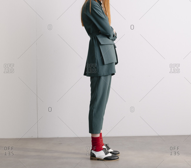 Green designer suit and red socks worn by model in front of a white wall