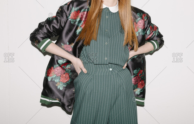 Young model wearing a silky floral jacket over green striped outfit