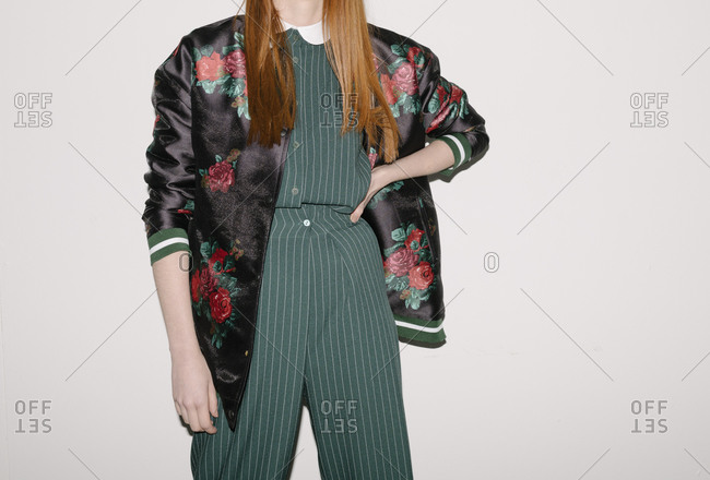 Model wearing a silky floral jacket over green striped outfit