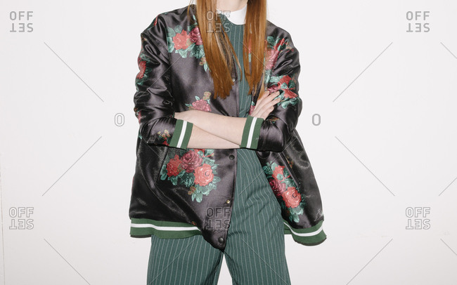 Young model wearing a silky floral jacket over green striped outfit with her arms crossed