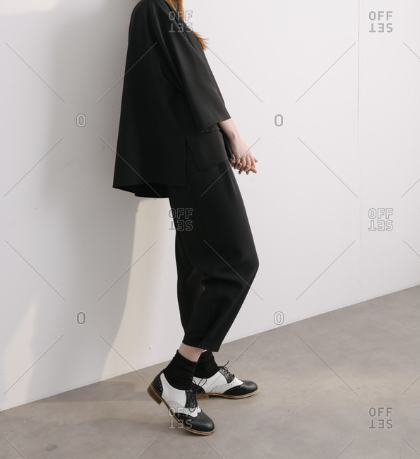 Young woman wearing black masculine designer outfit and retro oxford shoes