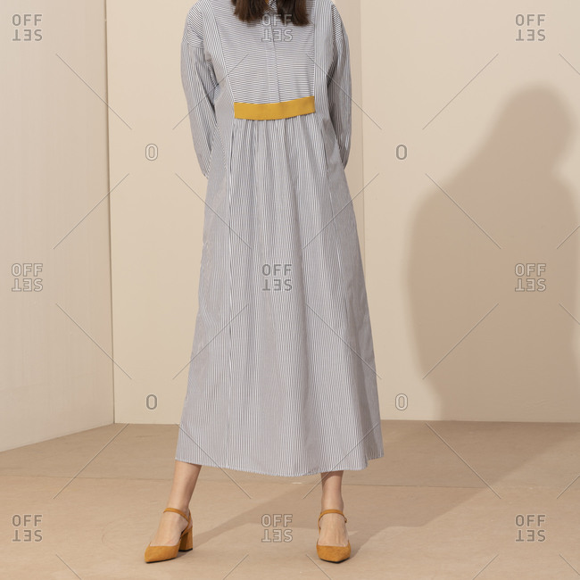 Studio shot of model wearing casual striped dress and yellow shoes