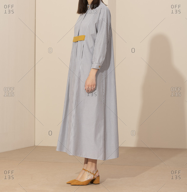 Side view of model wearing casual striped dress and yellow shoes