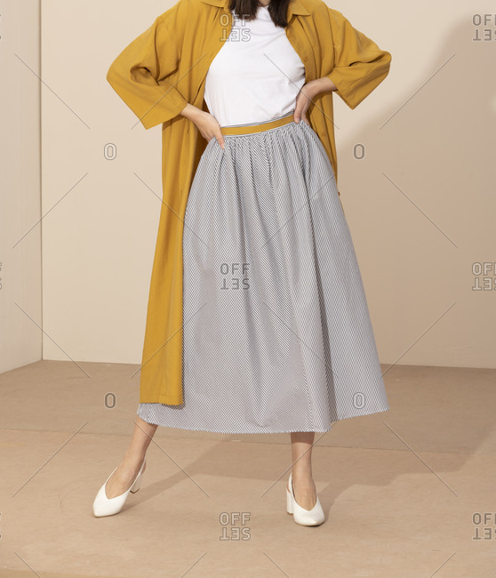 Woman wearing flowing striped skirt and long yellow jacket and standing with her hands on her hips