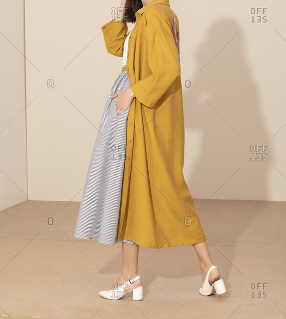Side view of woman wearing flowing striped skirt and long yellow jacket