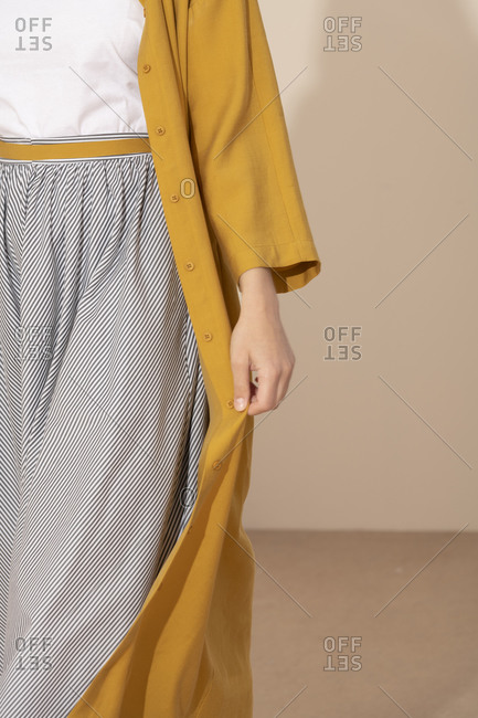 Close up of woman wearing flowing striped skirt and long yellow jacket