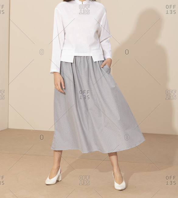 Model wearing casual striped skirt and white blouse