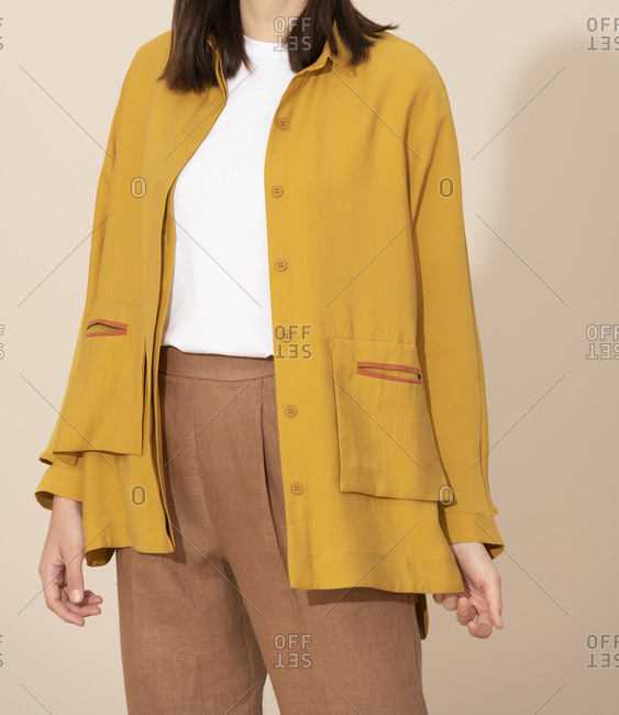 Woman wearing casual yellow jacket and brown slacks