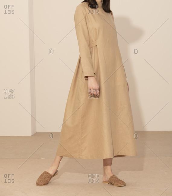 Studio shot of model wearing casual tan dress and shoes