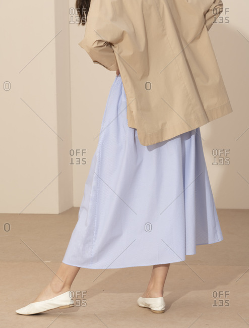 Back view of a lady wearing a simply blue striped skirt and tan jacket