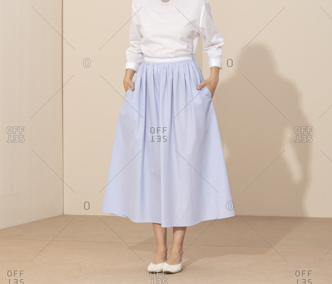 Woman standing with her hands in the pockets of her simple blue striped skirt