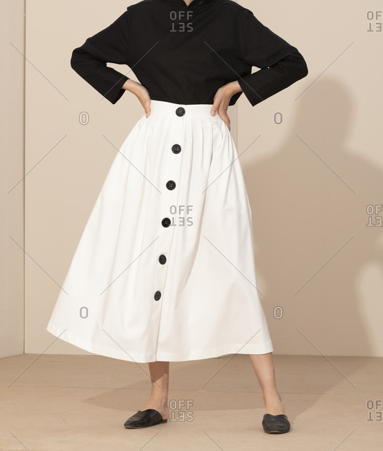 Young woman wearing a simple black top and white skirt with buttons