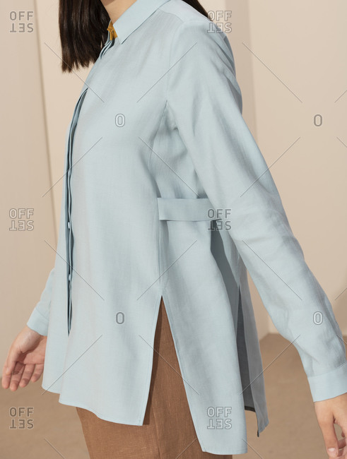 Close up of a model wearing a pastel blue blouse and tan slacks