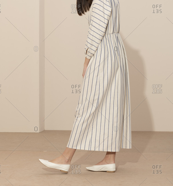 Side vie of a model wearing a blue and white striped casual dress