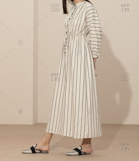 Side view of model wearing a black and white striped casual dress and loafer style mules