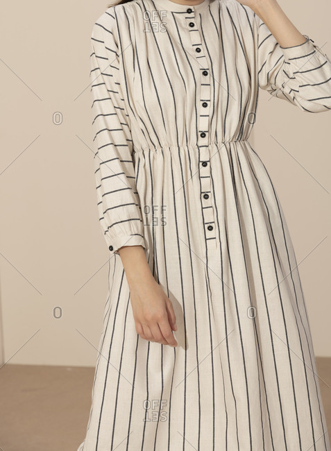 Close up of model wearing a black and white striped casual dress with buttons