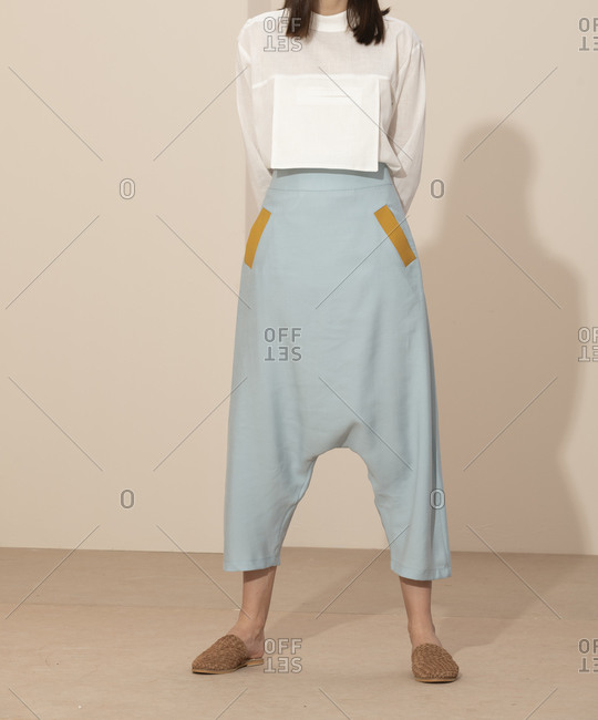 Model wearing pastel blue drop-crotch style pants and a white blouse with large pocket