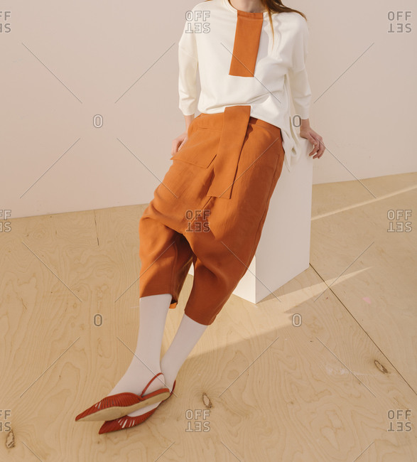 Model wearing orange drop-crotch style pants and a white blouse