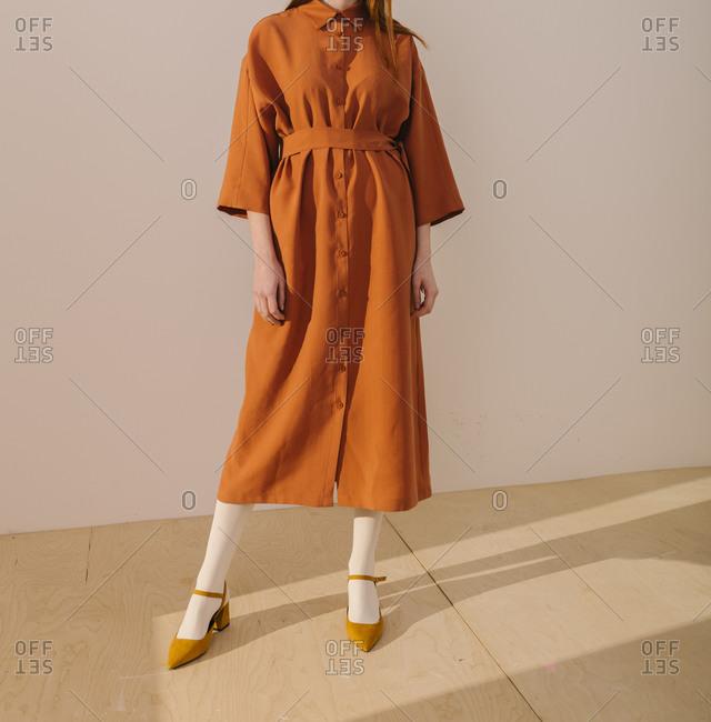 Studio shot of model wearing an orange casual dress and yellow shoes