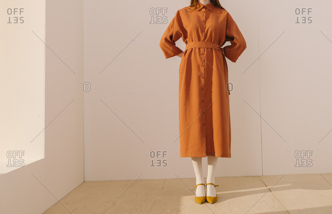 Studio shot of model wearing an orange casual dress with her hands behind her back