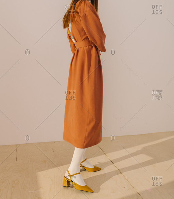 Side view of model wearing an orange casual dress and yellow shoes