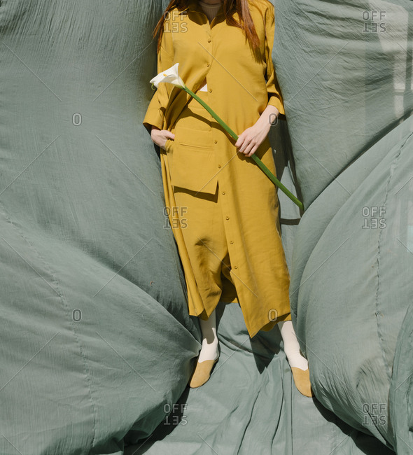 Woman wearing mustard yellow outfit with a drop-crotch and large pocket holding a calla lily