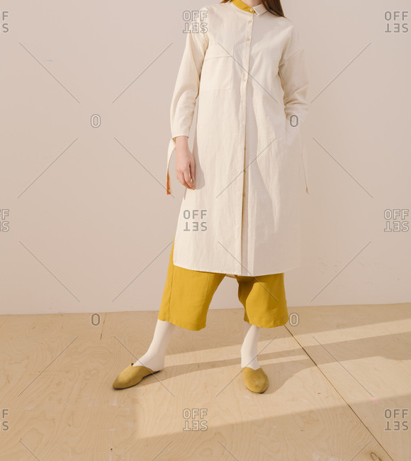 Model wearing a yellow outfit covered by a long white blouse