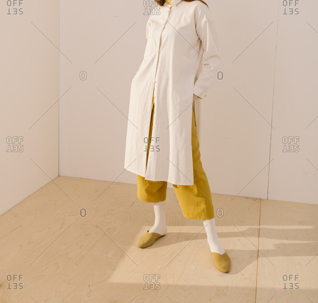 Studio shot of a model wearing a long white blouse over yellow pants