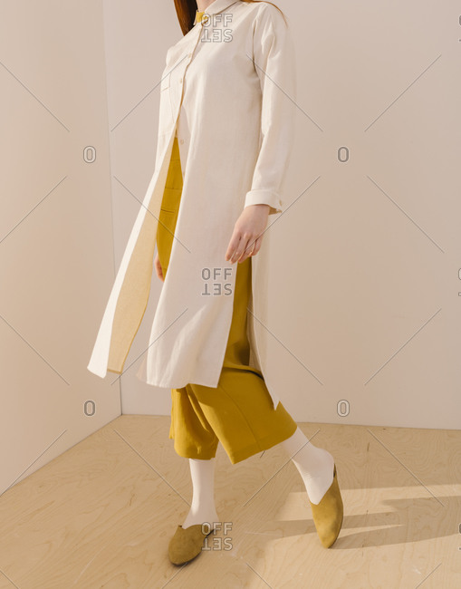 Model wearing a long white blouse over a yellow outfit
