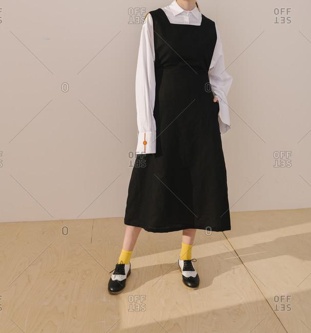 Studio shot of model wearing casual black dress with yellow socks