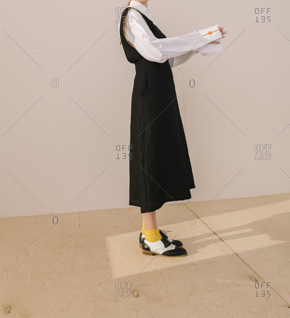 Side view of model wearing casual black dress with yellow socks