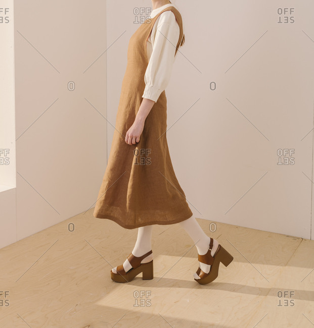 Side view of a model wearing a wrinkled brown dress and matching sandals