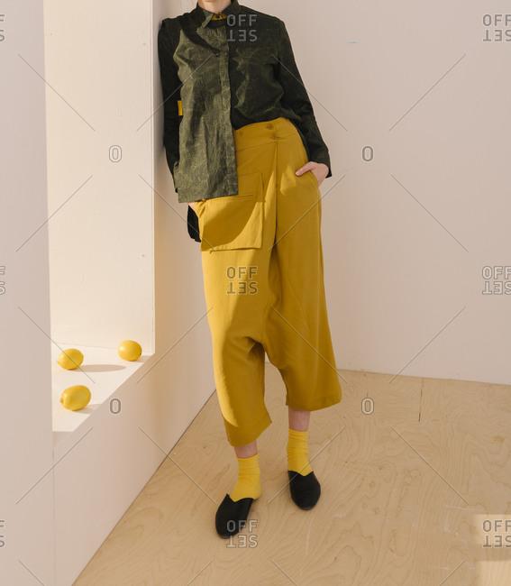 Model wearing long-crotch pants and green blouse by lemons on a windowsill