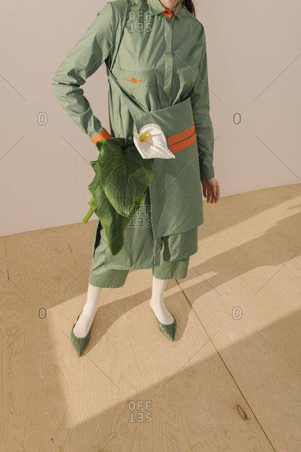 Model dressed in a light green outfit with orange detail holding a white calla lily