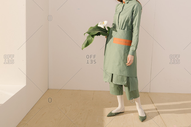 Model standing by window dressed in a light green outfit with orange detail holding a white calla lily