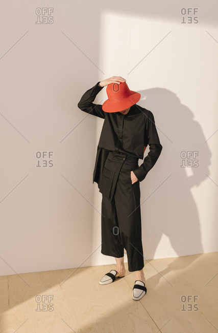 Studio shot of model wearing black outfit and red hat