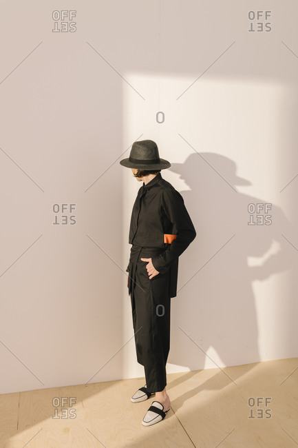 Studio shot of model wearing black outfit and hat looking back at wall