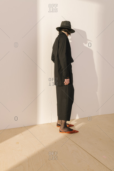 Studio shot of model wearing black outfit and hat with orange shoes